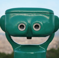 Green public binoculars where the eyeholes and shape create the illusion of a happy face